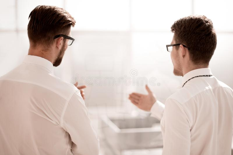 Rear view.business colleagues talk standing in a bright office stock image