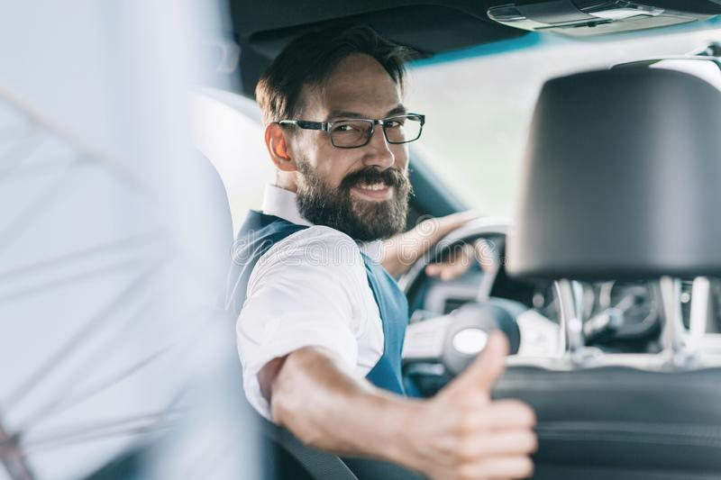 Rear view.business man sitting behind the wheel of a car stock image