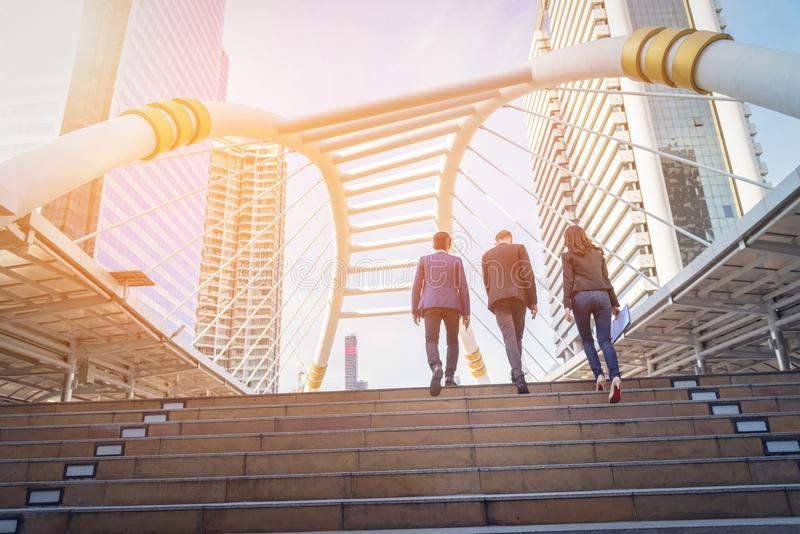 Rear view of business team climbing stairs go to a city. Business concept stock photos
