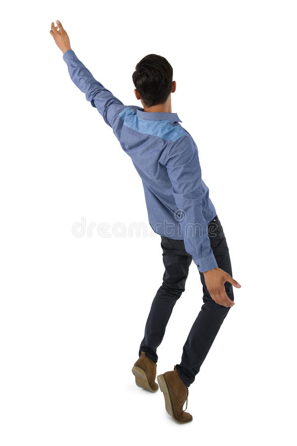 Rear view of businessman balancing. Against white background stock images