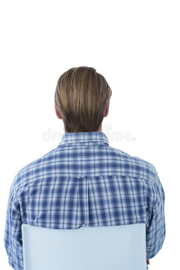 Rear view of businessman with brown hair sitting on chair. Against white background stock photography