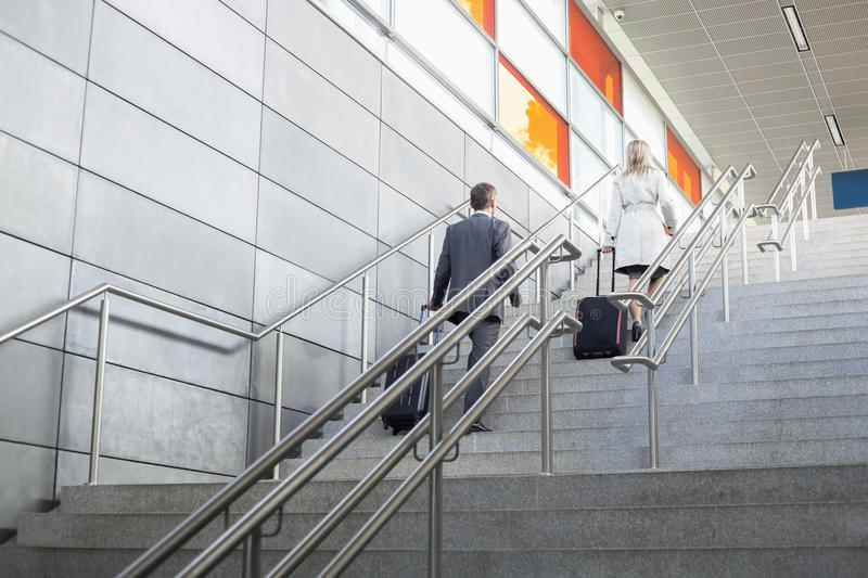 Rear view of businessman and businesswoman with luggage moving upstairs in railroad station stock images