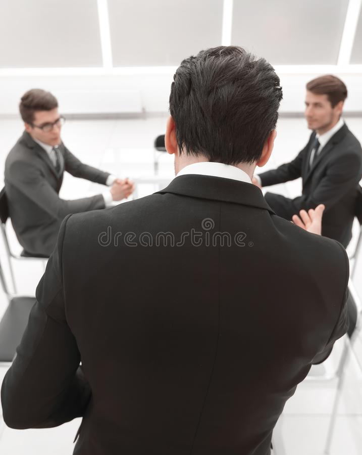 Rear view.businessman explaining business to the team new tasks royalty free stock images