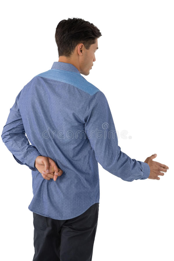 Rear view of businessman extending arm for handshake with fingers crossed. Against white background royalty free stock image