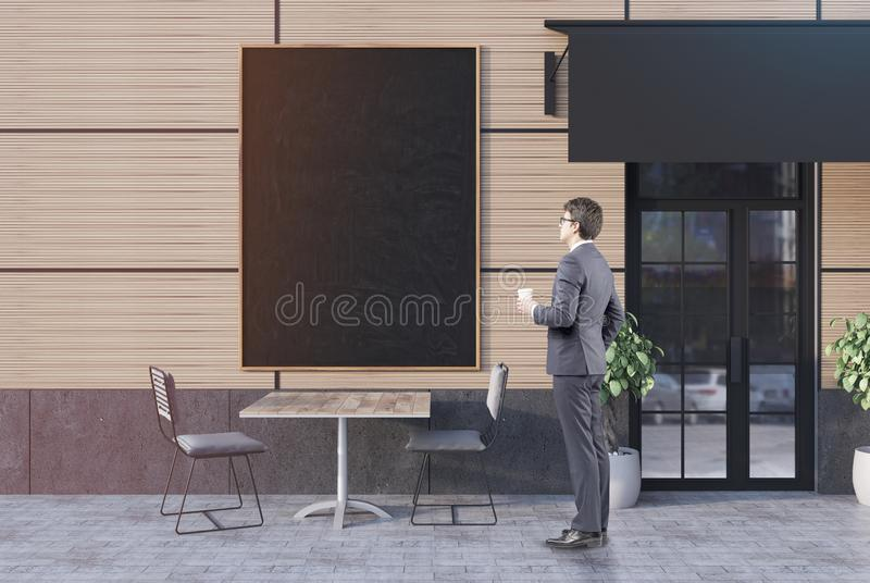 Businessman with coffee near a cafe, banner stock photo