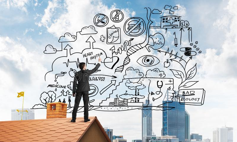 Rear view of businessman on house roof drawing his new business strategy. Mixed media stock photo