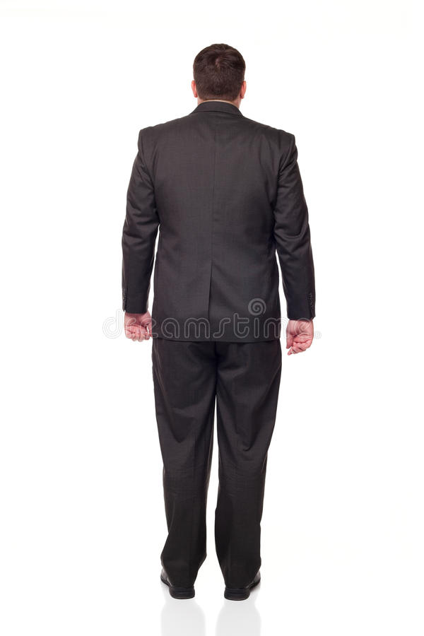 Rear view businessman looking away from camera. Isolated full length studio shot of the back side of a businessman facing away from the camera stock photo
