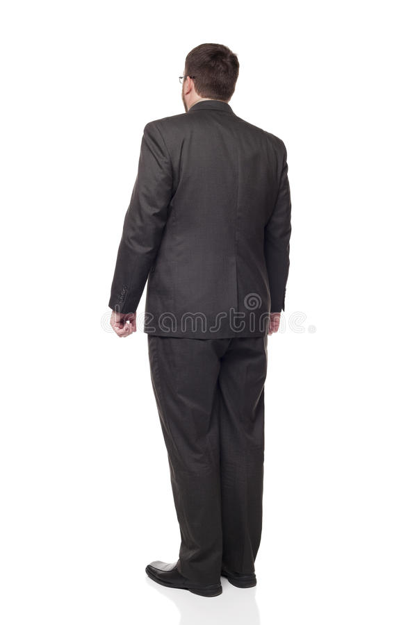 Rear view businessman looking away full length. Isolated full length studio shot of the rear view of a businessman in full suit looking away from the camera royalty free stock photography