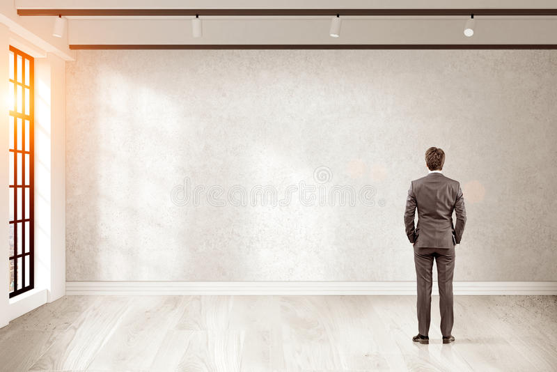 Rear view of businessman looking at blank wall of his office stock photography