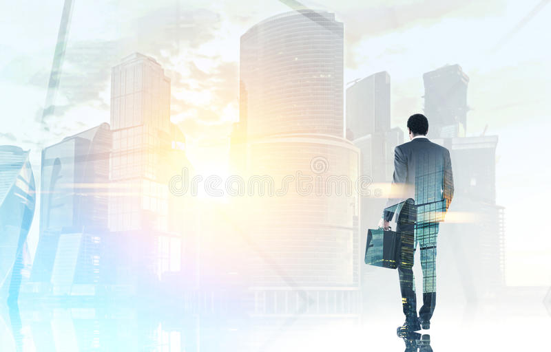 Rear view of a businessman looking at a city. Rear view of an African American businessman holding a suitcase and looking at a morning Moscow city. Toned image stock photography
