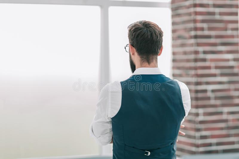 Rear view. businessman looking through office window. royalty free stock photo