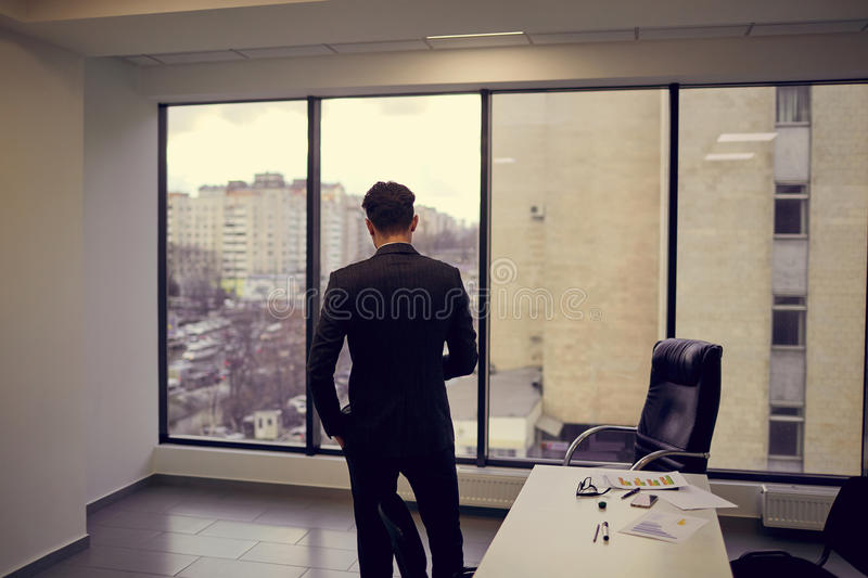 Rear view of a businessman in the office looking out window at n stock image