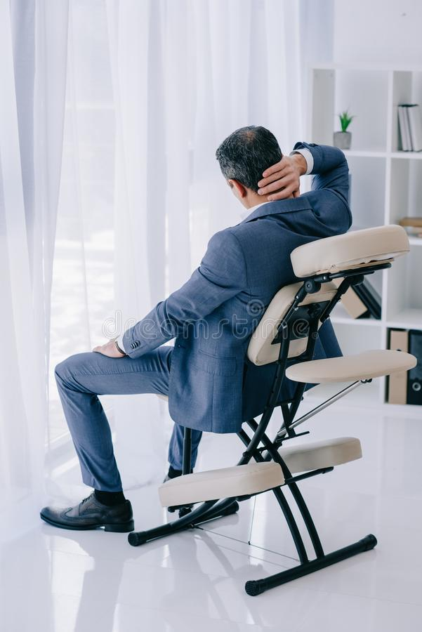rear view of businessman with painful backache sitting in massage chair stock photos