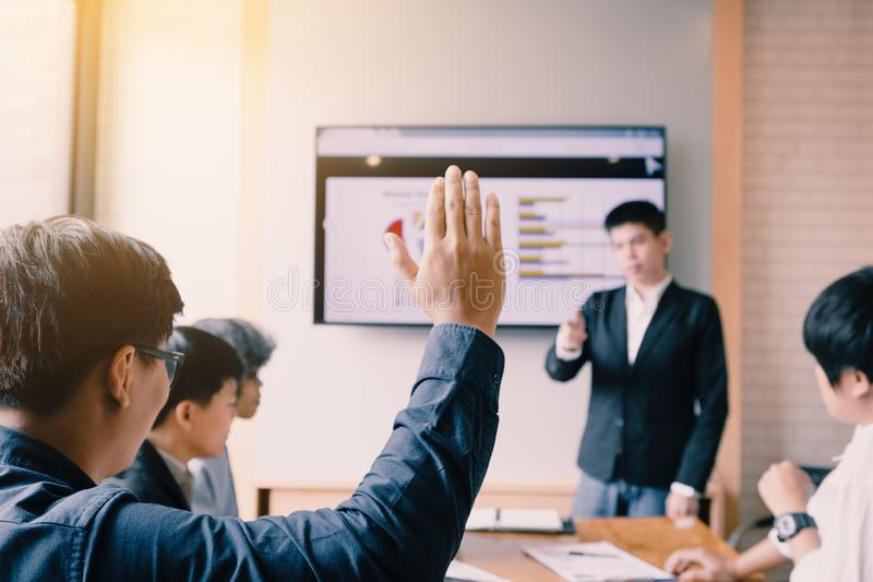 Rear view of a businessman raising hand wants to ask something i royalty free stock photography