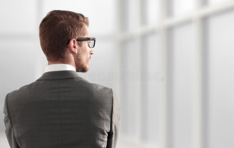 Rear view.businessman standing near the office window stock photography