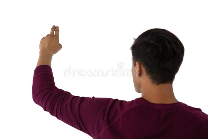 Rear view of businessman touching invisible imaginary screen. Against white baclground stock image