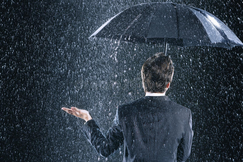 Rear View Of Businessman Under Umbrella In Rain royalty free stock photo