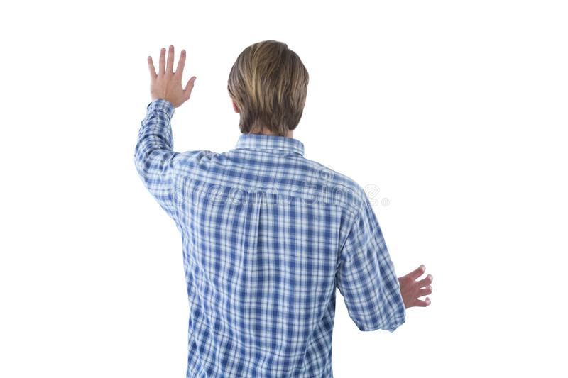Rear view of businessman using imaginary screen. Against white background stock photos