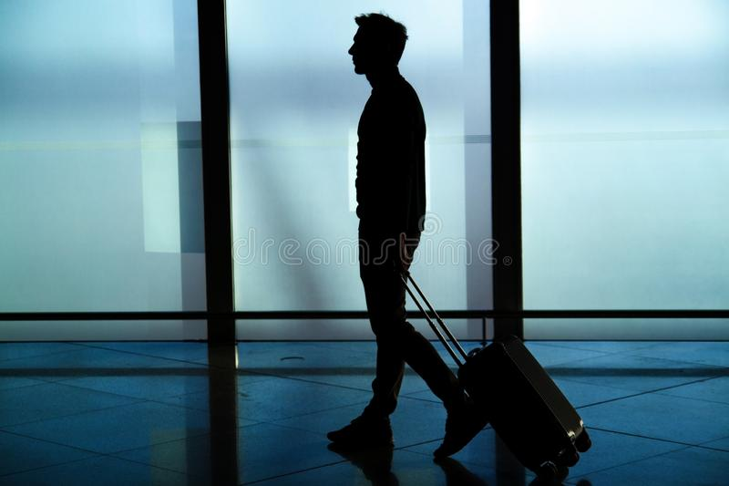 Rear view of businessman walking with bag outside airport. Young traveler pulling suitcase. royalty free stock image