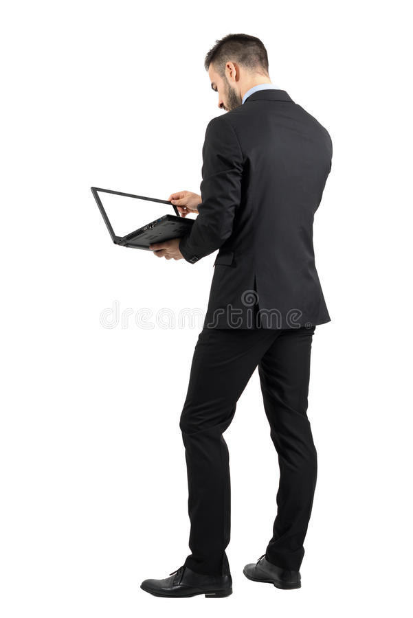 Rear view of businessman working on a laptop with blank empty screen. stock photo