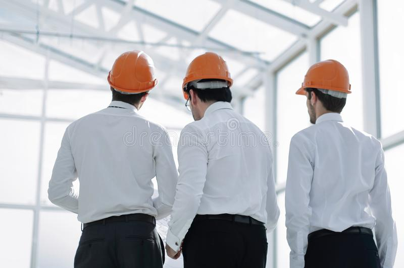 Rear view.businessmen in protective helmets standing in the new office royalty free stock photo