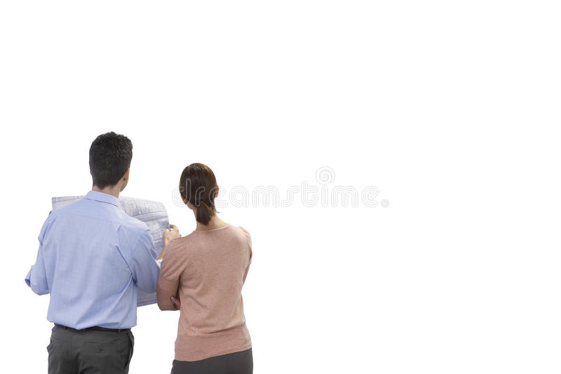 Download Rear View Of Businesspeople Holding Blueprint Against White Background Stock Photo - Image: 30856896