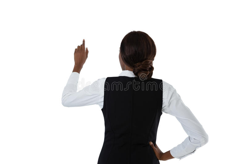 Rear view of businesswoman with hand on hip using invisible interface. Against white background royalty free stock image
