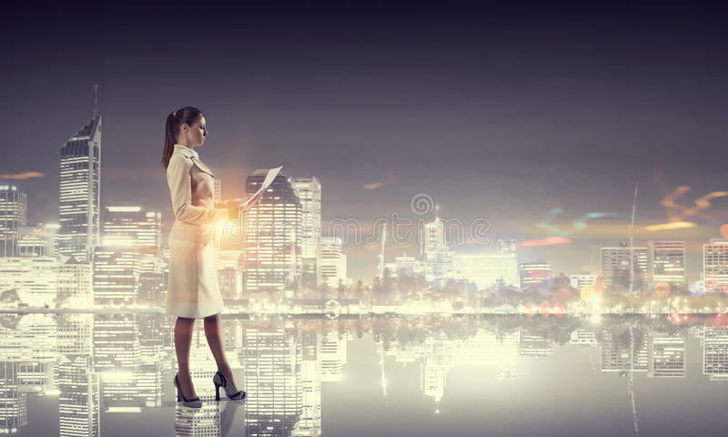 Rear view of businesswoman looking at night city. Young businesswoman with papers in hands against night city background stock photos