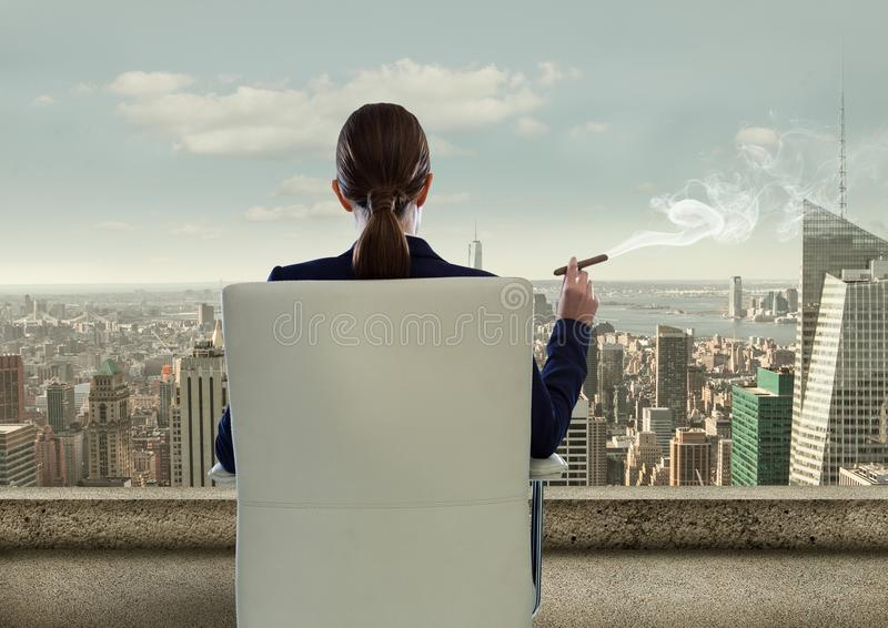 Rear view of businesswoman sitting on chair and looking at city while smoking cigar. Digital composite of Rear view of businesswoman sitting on chair and looking stock image