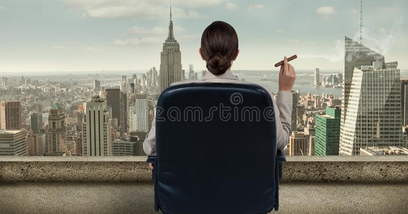 Rear view of businesswoman sitting on chair and looking at city while smoking cigar. Digital composite of Rear view of businesswoman sitting on chair and looking stock photo