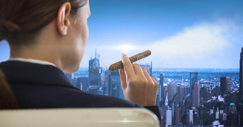 Rear view of businesswoman sitting in chair smoking looking at cityscape. Digital composite of Rear view of businesswoman sitting in chair smoking looking at stock images
