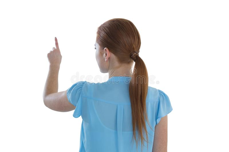 Rear view of businesswoman touching imaginary screen. Against white background stock images
