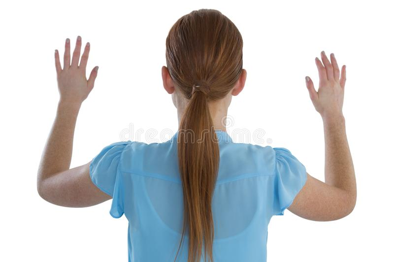 Rear view of businesswoman using imaginary screen. Against white background stock photo
