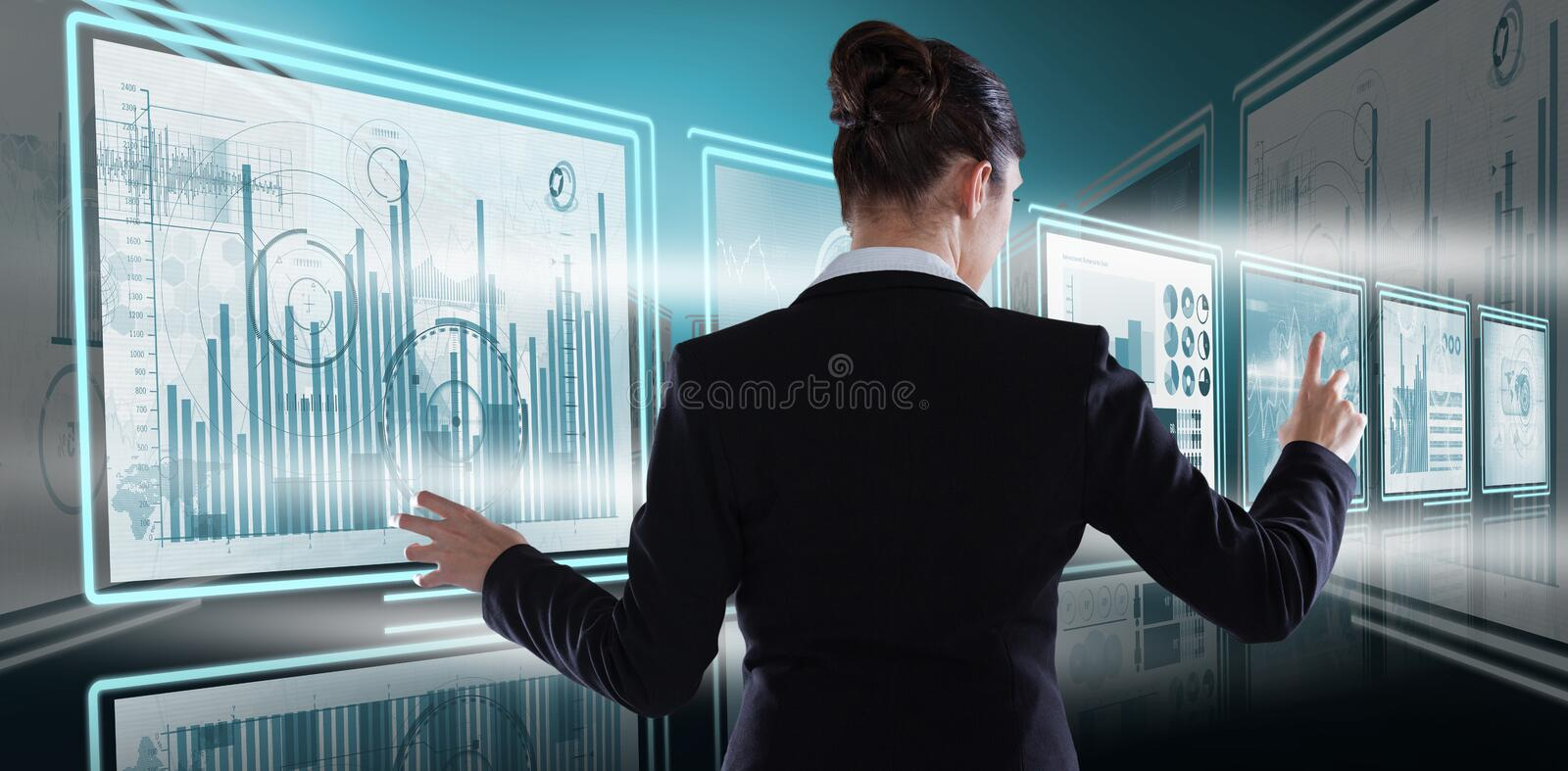 Composite image of rear view of businesswoman using imaginative digital screen stock images