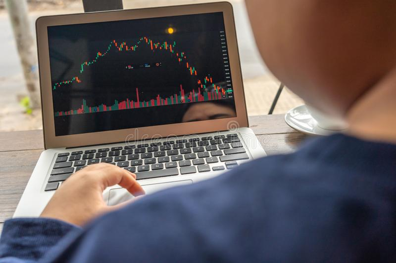 Rear view of businesswoman working on stock market trading graph. Asian businesswoman working on stock market trading graph on laptop royalty free stock images