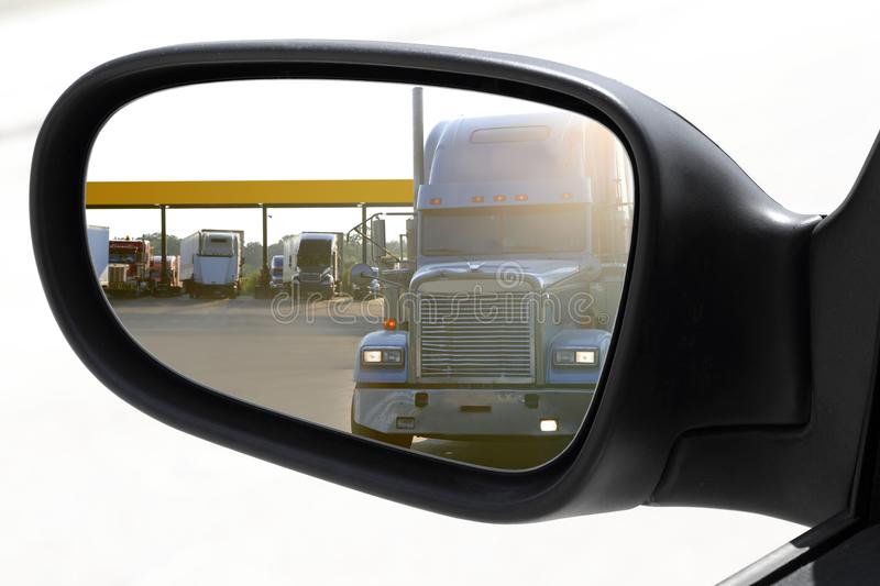 Rear view car driving mirror overtaking big truck. Lorry royalty free stock photo
