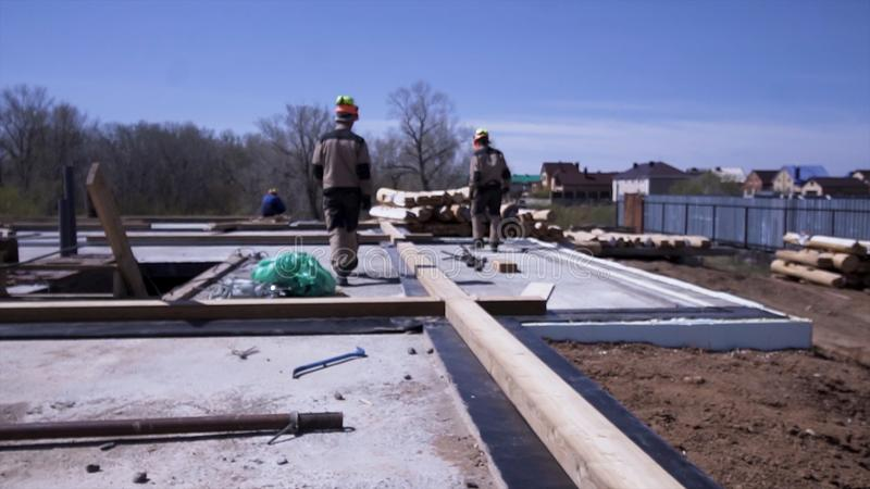 Rear view of carpenters in uniform during working process, building of a wooden house. Clip. Making the foundation of stock photography