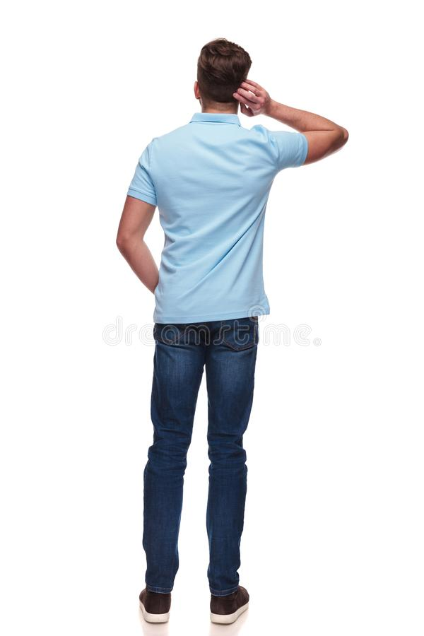 Rear view of casual man wearing a blue polo shirt. Standing on white background with hand in pocket, full body picture royalty free stock image