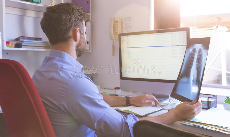 Male doctor checking  x ray report in computer at clinic. Rear view of Caucasian male doctor checking  x ray report in computer at clinic stock photography