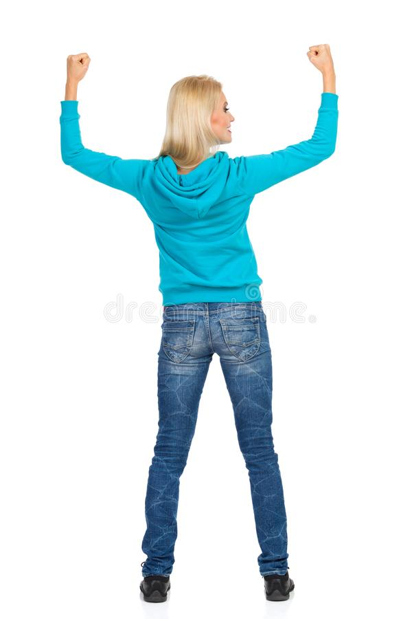Rear View Of Cheering Woman. Rear view of blond woman in turquoise sweater and jeans with arms raised and looking away. Full length studio shot isolated on white royalty free stock photos