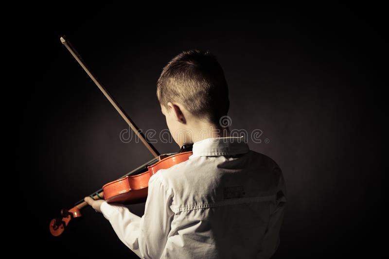 Rear view of child playing violin in darkened room royalty free stock photography