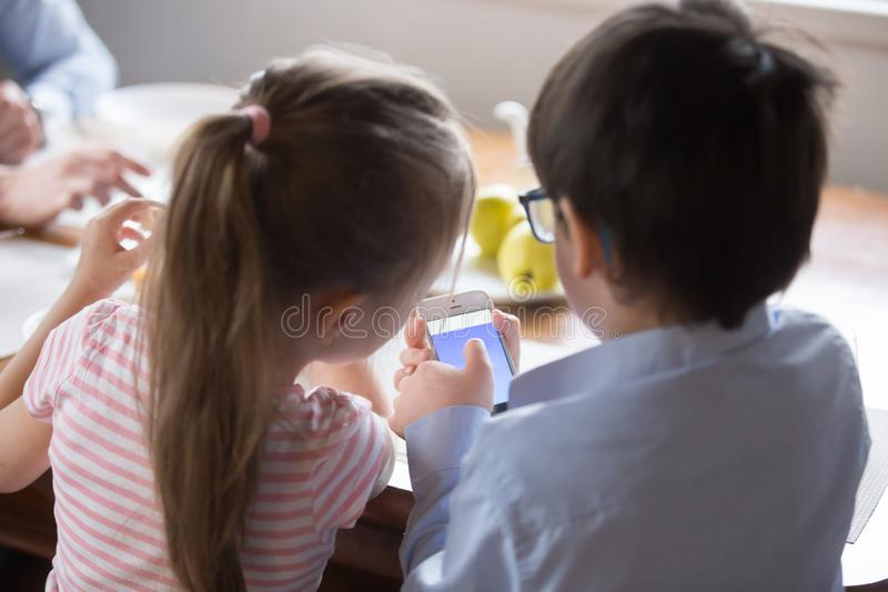 Rear view children using smartphone sitting in the kitchen royalty free stock photo