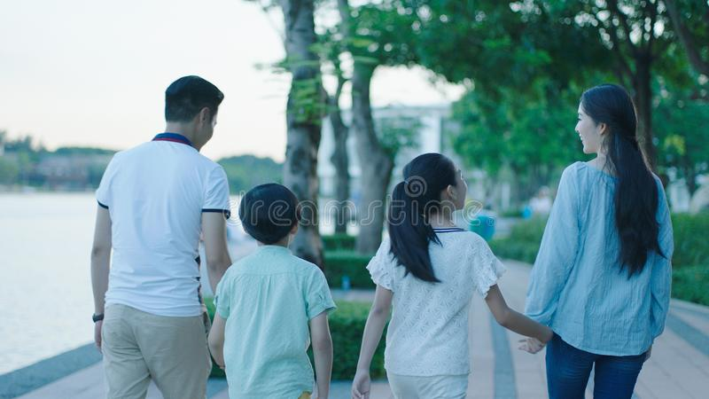 Rear view of Asian family smiling & walking on waterfront promenade at dusk stock photography