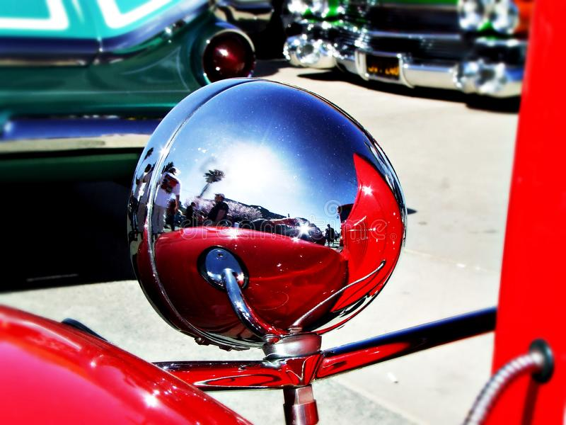 Rear view of chrome headlight on red roadster. Great reflections of people and palm trees and reflection the car itself. Very artistic colorful shot royalty free stock photo