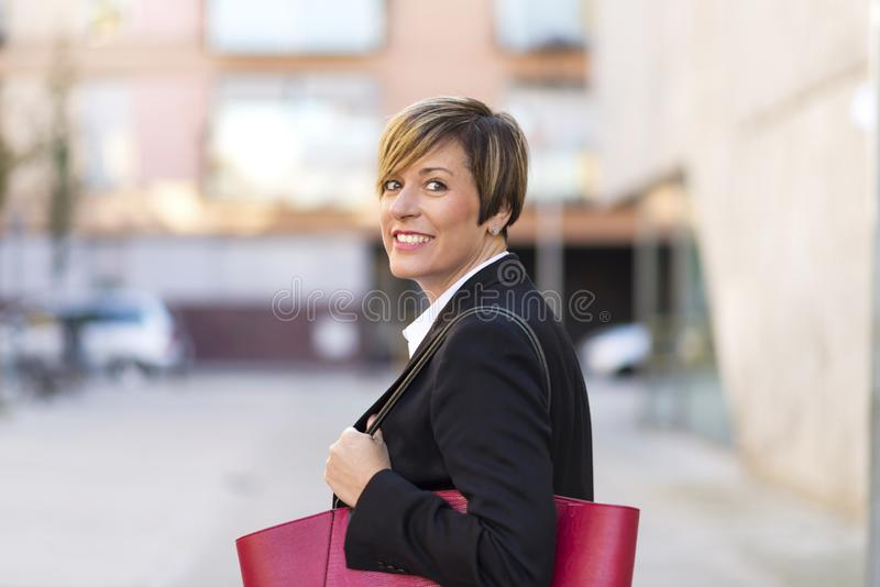 Rear view of confidence, elegant and smiling business woman standing on street while looking camera outdoors in sunny day royalty free stock image