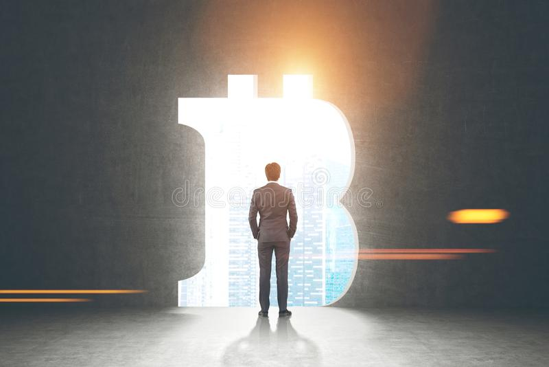 Confident businessman, bitcoin sign. Rear view of a confident businessman wearing a suit and looking at a cityscape standing in a dark room with a large bitcoin stock photos