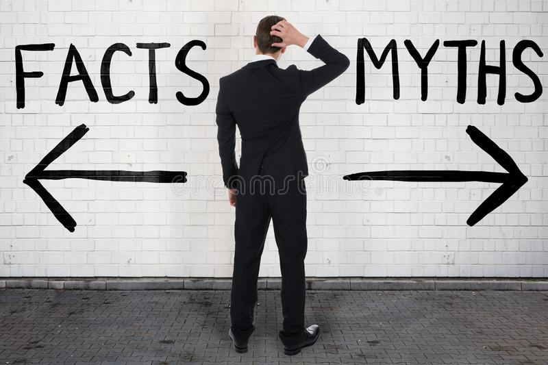 Businessman Looking At Arrow Signs Below Facts And Myths. Rear view of confused businessman looking at arrow signs below facts and myths text stock image