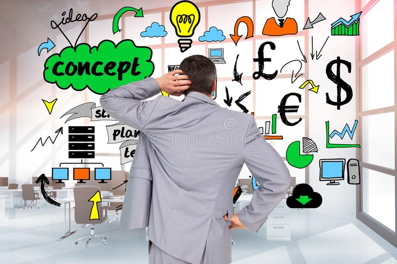 Rear view of confused businessman looking at doodle graphics on wall stock photography