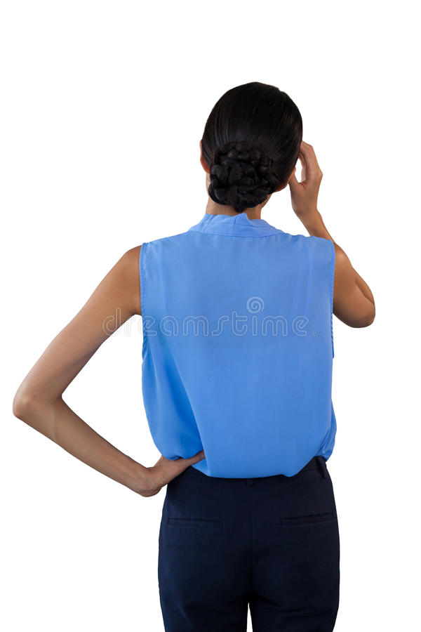 Rear view of confused businesswoman with head in hand. Against white background royalty free stock photo