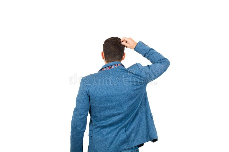 Rear view of confused young businessman, hand to head thoughtful gesture, isolated on white background. Business planning concept stock photos